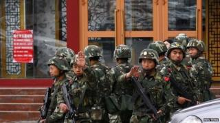 Paramilitary policemen gesture to stop a photographer from taking pictures as they stand guard after an explosives attack hit downtown Urumqi on Thursday, in the Xinjiang Uighur Autonomous Region 23 May 2014