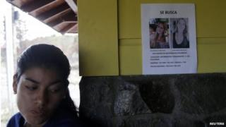 A woman stands next to a missing person flyer showing pictures of two missing Dutch women on a wall in the town of Boquete on 12 April, 2014