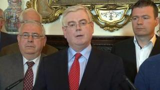 Eamon Gilmore, surrounded by party colleagues, announced he was standing down at a press conference in Dublin on Monday