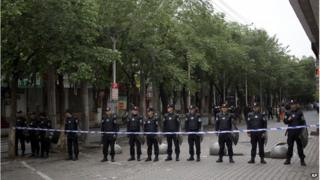 Policemen stand guard near the road leading to the site of Thursday's explosion in Urumqi, China's northwestern region of Xinjiang, Friday, 23 May.