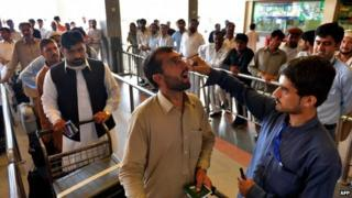 In this photograph taken on May 20, 2014, a Pakistani health worker administers polio vaccination drops to a traveller at the Peshawar International Airport in Peshawar.