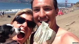 Man, woman and dog on beach holding some cash