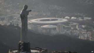 An aerial view shot of the Maracana stadium behind the Christ the Redeemer statue in Rio de Janeiro