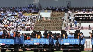Trucks carrying criminals and suspects are seen during a mass sentencing rally at a stadium in Yili, Xinjiang Uighur Autonomous Region, 27 May 2014