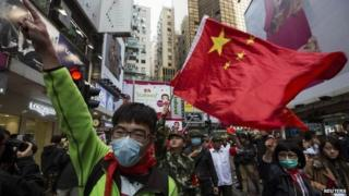 Protesters wave Chinese national flags during an anti-mainland tourist rally in Hong Kong's famous Causeway Bay shopping district, 16 March 2014