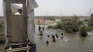 This May 12, 2006 file photograph shows a slum resident (L) as he uses a toilet that opens into the water below as children swim in the water near a protest rally against the government for demolishing make-shift huts at Mandala in Mankhurd in north central Mumbai.