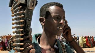 A Somali militant talks on a mobile phone