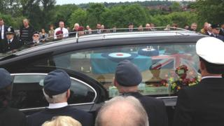 Hearse carrying coffin draped in RAF flag
