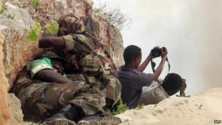 African Union peacekeepers take cover, 15 May 2007, as two Somali photographers point their cameras towards the site where the troops were detonating seized ammunition in Mogadishu, Somalia