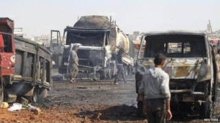 File photo: People walk near burnt trucks and fuel tankers at a fuel market hit by a car bomb in the Maarat Al-Naasan area of Idlib, Syria, 28 May 2014