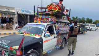 Pakistani soldier inspects truck loaded with belongings