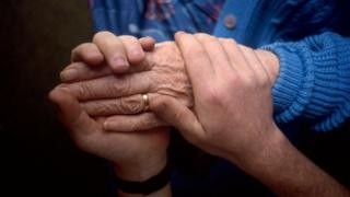 Carer helping old person