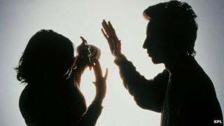 Silhouette of man striking woman