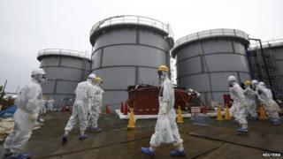 File photo: Journalists and Tepco employees wearing protective suits and masks walk past storage tanks for radioactive water at the tsunami-crippled Fukushima Daiichi nuclear power plant in Fukushima prefecture, Japan, 7 November 2013