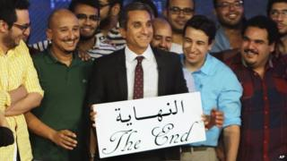 "Egyptian satirist Bassem Youssef, who is known as ""Egypt's Jon Stewart,"" poses with his team with an English and Arabic placard reading ""the end,"" during a press conference in Cairo, Egypt, Monday, June 2"