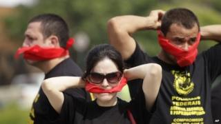 """Federal police wearing T-shirts that read in Portuguese """"SOS Federal Police"""" cover their mouths with bandanas in Rio de Janeiro on 7 May, 2014"""