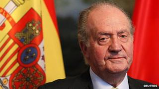 Spain's King Juan Carlos in front of a Spanish flag in 2011