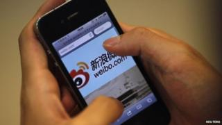 File photo: A man visits Sina's weibo microblogging site using an iPhone in Shanghai