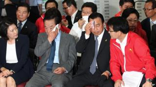 Lee Wan-goo, floor leader of the ruling Saenuri Party, and Suh Chung-won, Chairman of the Party's campaign, wipe the sweat off their faces as they watch a television program broadcasting the election exit polls in Seoul, South Korea, on Wednesday, 4 June, 2014
