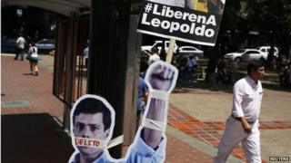"People walk past cardboard figures of jailed opposition leader Leopoldo Lopez with his mouth covered with the word ""crime"" during a gathering in support of him in Caracas on 4 June,, 2014"