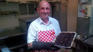 The Cook Shop's owner Nigel Brazier holding a tray of faggots