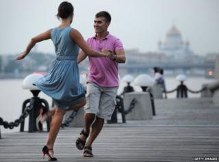 Muscovites dance on the embankment of the Moskva river in central Moscow late evening