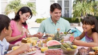 A family eats a meal outside a house.