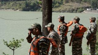 Indian rescue personnel gather on the banks of the Beas River during a search operation in Kullu on June 9, 2014.