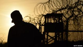 A soldier is silhouetted against the sky on the Guantanamo Bay detention facility.