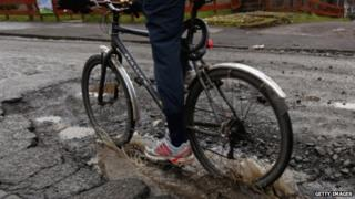 Cyclist riding through pothole (generic)
