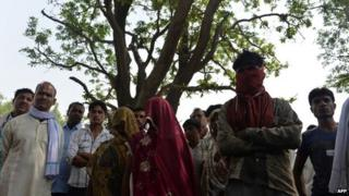 In this May 31, 2014, photo mothers of gang-rape victims (C, shawls covering their faces) and villagers stand in front of the mango tree where the girls were hanged in Katra Shahadatgunj in Badaun district