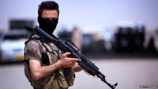 Member of the Kurdish security forces is holding a weapon