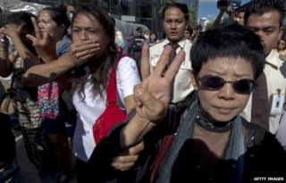 A woman in Thailand doing a three-finger salute