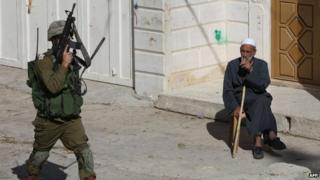 An Israeli soldier walks past a Palestinian man sitting on a street in the West Bank town of Hebron