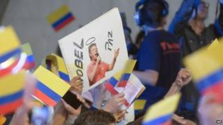"""A supporter of President Juan Manuel Santos holds a sign which reads in Spanish """"Nobel Peace Prize"""" during his victory rally in Bogota on 15 June, 2014"""