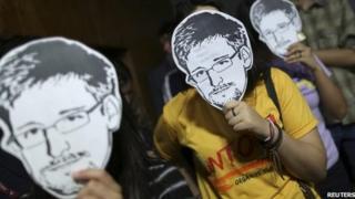People holding Edward Snowden masks