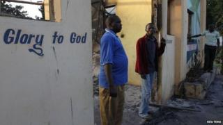 Residents of Kibaoni look at the ruins of the burnt down Breeze View Hotel after unidentified gunmen attacked the coastal Kenyan town of Mpeketoni June 16, 2014.