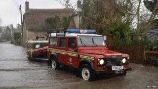An emergency services vehicle pulls a boat through flood waters in the village of Thorney