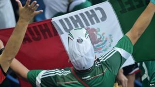 A Mexican football fan celebrates at the end of the Group A football match between Mexico and Cameroon on 13 June 2014