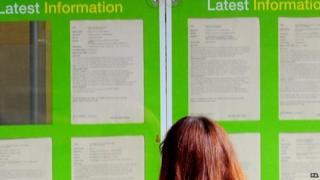 A woman looks at a JobCentre list of vacancies