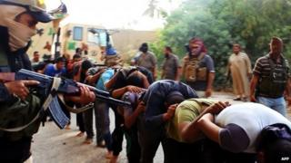 A masked ISIS militant aiming a gun at captured Iraqi men