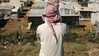 A man looking at a Syrian refugee camp in the Lebanese village of Zahle in the Bekaa valley on 17 June 2014.