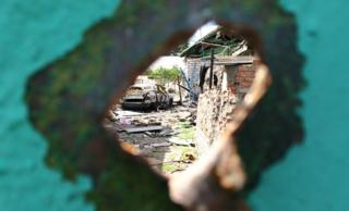 View through a hole in a wall caused by shrapnel shows destroyed building and burned out car in Marakove