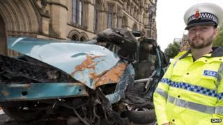Insp Matt Bailey-Smith with a car wreckage