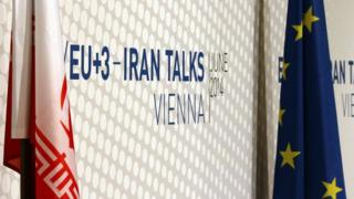 Iranian and EU flags stand in front of a poster of Iran talks in Vienna, Austria. 20 June 2014