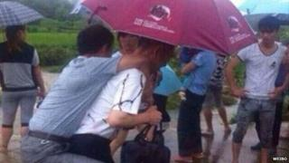 A man wearing leather shoes being carried on another man's back through ankle-deep water in Lantian Village