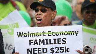 A woman holds up a sign at an anti-Walmart protest.