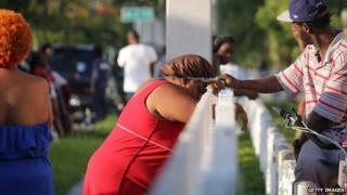 Hermonya Richardson, in red (C), mother of shooting victim Kevin Richardson, 30, reacts to the death of her son who was gunned down outside an apartment complex in Miami's Liberty City neighbourhood, 24 June 2014