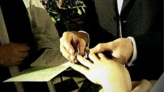 Man puts ring on woman's finger