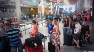 Passengers from Belfast flight queue in Airport